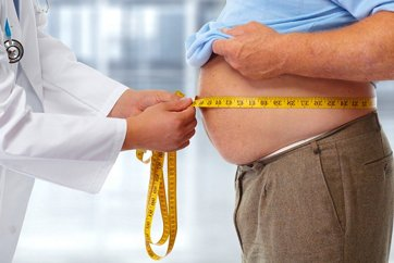 A photo of a man with obesity being evaluated by a physician
