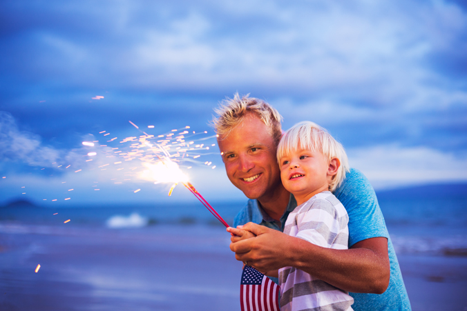 Dad and young son holding sparklers with US flag