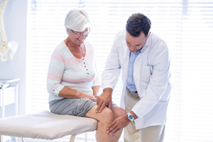 Physicians performing physical therapy on older women for knee injury
